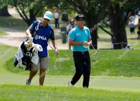 Brain Gay, right, walks to the 18th green with his caddie Chris Berry during the first round of the PGA Championship golf tournament at Bellerive Country Club, in St. Louis