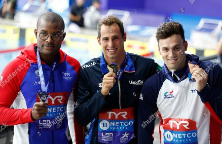 Silver medalist Mehdy Metella of France, left, gold medalist Piero Codia of Italy, bronze medalist James Guy of Great Britain pose on the podium of the 100 meters butterfly men final at the European Swimming Championships in Glasgow, Scotland