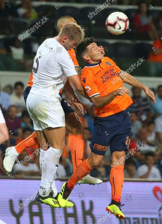 Burnley's Charlie Taylor, left, fights for the ball with Istanbul Basaksehir's Manuel da Costa, obscured, and Milos Jojic, right, during the Europa League qualification soccer match between Istanbul Basaksehir and Burnley, at the Fatih Terim stadium in Istanbul