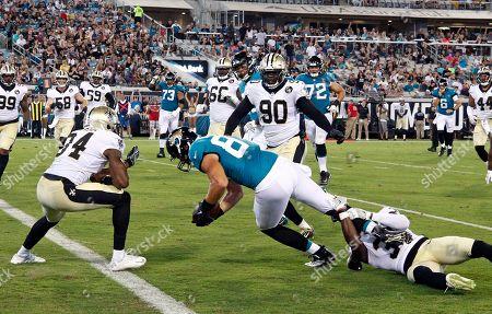 Stock Image of Jacksonville Jaguars tight end Scott Orndoff, center, scores a touchdown despite defensive effort by New Orleans Saints defensive back Chris Banjo, right, and defensive back Charlie Miller (34) during the second half of an NFL preseason football game, in Jacksonville, Fla