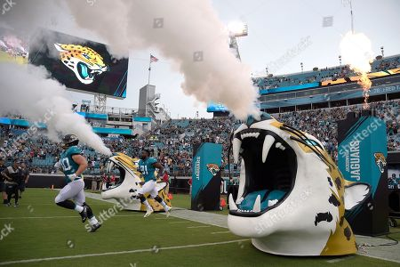 Jacksonville Jaguars running back Tommy Bohanon (40) and defensive end Yannick Ngakoue (91) run onto the field during team introductions before an NFL preseason football game against the New Orleans Saints, in Jacksonville, Fla