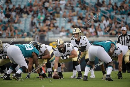 New Orleans Saints quarterback Tom Savage (12) sets up behind center Max Unger (60) in front of Jacksonville Jaguars defensive tackle Marcell Dareus (99) during the first half of an NFL preseason football game against the Jacksonville Jaguars, in Jacksonville, Fla