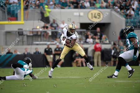 New Orleans Saints wide receiver Michael Thomas (13) catches a pass in front of Jacksonville Jaguars linebacker Blair Brown (53) and cornerback Tre Herndon, left, during the first half of an NFL preseason football game, in Jacksonville, Fla
