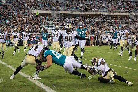 Jacksonville Jaguars tight end Scott Orndoff, center, scores a touchdown despite defensive effort by New Orleans Saints defensive back Chris Banjo, right, and defensive back Charlie Miller (34) during the second half of an NFL preseason football game, in Jacksonville, Fla