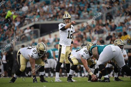 New Orleans Saints quarterback Tom Savage (12) calls out signals behind offensive guard Larry Warford (67), center Max Unger (60) and offensive guard Josh LeRibeus, right, during the first half of an NFL preseason football game against the Jacksonville Jaguars, in Jacksonville, Fla