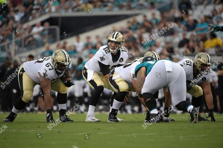 New Orleans Saints quarterback Tom Savage (12) calls out signals behind offensive guard Larry Warford (67), center Max Unger (60) and offensive guard Josh LeRibeus (61) during the first half of an NFL preseason football game against the Jacksonville Jaguars, in Jacksonville, Fla