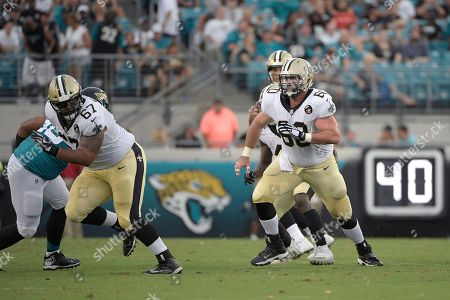 New Orleans Saints offensive guard Larry Warford (67) and center Max Unger (60) set up to block during the first half of an NFL preseason football game against the Jacksonville Jaguars, in Jacksonville, Fla