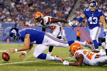 New York Giants' Zak DeOssie, left, recovers a fumble as Cleveland Browns' Orson Charles (82) closes in during the second half of a preseason NFL football game, in East Rutherford, N.J