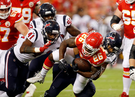 Kansas City Chiefs running back Damien Williams (26) is brought down by Houston Texans linebacker Dylan Cole (51) and linebacker Zach Cunningham (41) during the first half of an NFL preseason football game in Kansas City, Mo