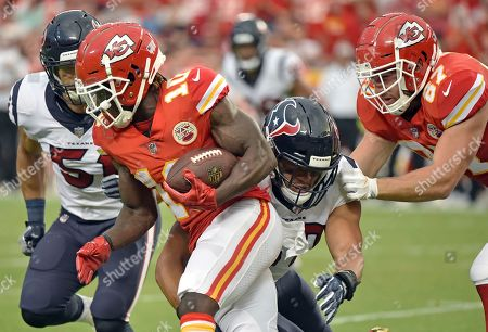 Kansas City Chiefs wide receiver Tyreek Hill (10) runs with the ball away from a tackle attempt by Houston Texans linebacker Dylan Cole (51) and linebacker Brennan Scarlett, second from right, who is blocked by tight end Travis Kelce (87) during the first half of an NFL preseason football game in Kansas City, Mo