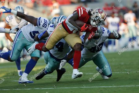 San Francisco 49ers running back Jerick McKinnon, foreground, runs against Dallas Cowboys defensive end Datone Jones (56), linebacker Jaylon Smith, center left, and linebacker Joe Thomas (48) during the first half of an NFL preseason football game in Santa Clara, Calif