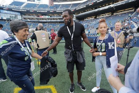 Former Seattle Seahawks strong safety Kam Chancellor, center, walks with his wife Tiffany, right, before an NFL football preseason game against the Indianapolis Colts, in Seattle