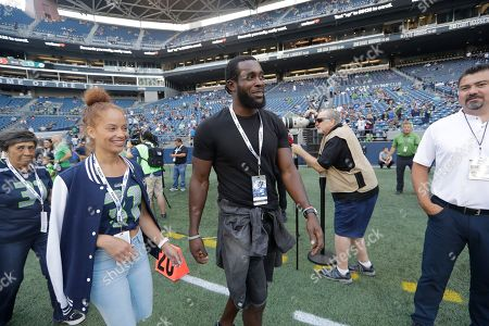 Stock Image of Former Seattle Seahawks strong safety Kam Chancellor, center, walks with his wife Tiffany before an NFL football preseason game against the Indianapolis Colts, in Seattle