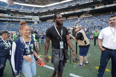 Former Seattle Seahawks strong safety Kam Chancellor, center, walks with his wife Tiffany before an NFL football preseason game against the Indianapolis Colts, in Seattle