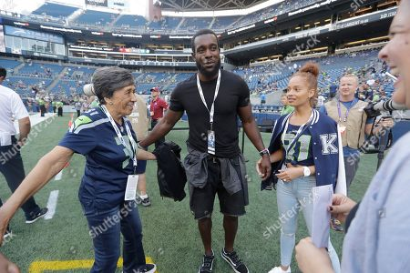 Former Seattle Seahawks strong safety Kam Chancellor, center, stands with his wife Tiffany, right, before an NFL football preseason game against the Indianapolis Colts, in Seattle