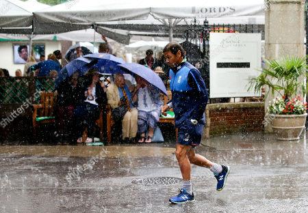 Mark Ramprakash makes a dash for cover during torrential rain