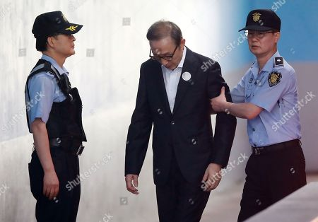 Former South Korean President Lee Myung-bak (C) is escorted by security personnel as he enters the Seoul Central District Court in Seoul, 10 August 2018, to attend a hearing in his trial on corruption charges. (Attention editors: Badge on suit pixelated by source)