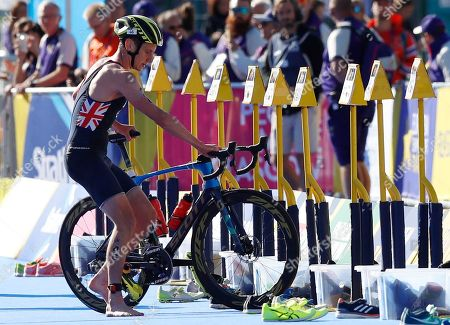 Alistair Brownlee of Great Britain dismounts his bike as he prepares to participate in the running discipline of the men's triathlon finals at Strathclyde Country Park during the European Championships in North Lanarkshire, Scotland