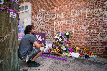 Ryan Bailey 'offers a blessing' next to a memorial for Heather Heyer, a 32-year-old woman who was killed at the spot one year ago when a white supremacist plowed his car into protestors in Charlottesville, Virginia, USA, 10 August 2018. On 12 August 2017, a bloody clash between white supremacists and counter protestors in Charlottesville left three people dead and dozens injured.