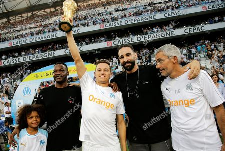 Steve Mandanda (2-L) of Olympique Marseille, Florian Thauvin (C), Adil Rami (2-R) and Franck Le Gall (R) pose with World Cup before  the French Ligue 1 soccer match, Olympique Marseille vs Toulouse FC at the Velodrome Stadium in Marseille, southern France, 10 August 2018.