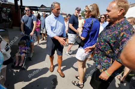 Former House Speaker John Boehner greets fairgoers after listening to U.S. Rep. John Delaney, D-Md., speak at the Des Moines Register Soapbox during a visit to the Iowa State Fair, in Des Moines, Iowa