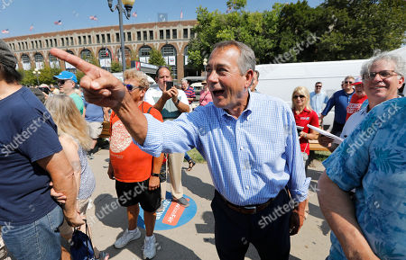 Former House Speaker John Boehner listens to Rep. John Delaney, D-Md., speak to at the Des Moines Register Soapbox during a visit to the Iowa State Fair, in Des Moines, Iowa