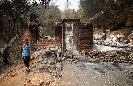 Emily Scott stands near the ruins of her house burned in the Carr Fire, in Shasta, Calif