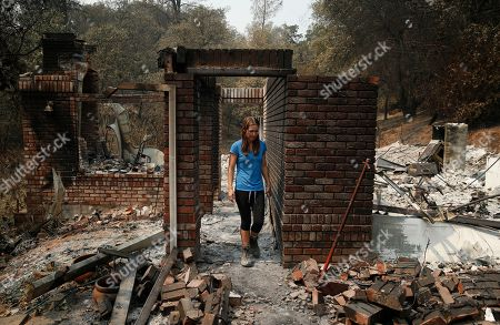Emily Scott walks through the ruins of her house burned in the Carr Fire, in Shasta, Calif