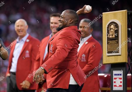 Vladimir Guerrero, Mike Witt, Chuck Finley, Garret Anderson. Former Los Angeles Angels player Vladimir Guerrero throws out the ceremonial first pitch as Mike Witt, left, Chuck Finley, second from left, and Garret Anderson watch during a ceremony to celebrate his induction into the Baseball Hall of Fame, prior to a baseball game between the Angels and the Oakland Athletics, in Anaheim, Calif