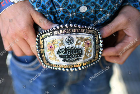 Stock Image of Ten year-old Riley Schmidt shows off his winner's buckle after winning the Poddy Calf Ride final event at the Mount Isa Mines Rotary Rodeo, Queensland, Australia, 11 August 2018. This is the 60th anniversary of the rodeo, the biggest of its kind in the Southern Hemisphere.