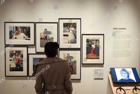 A member of the media looks at photographs during a media preview of the 'Heath Ledger: A Life In Pictures' exhibition at the National Film and Sound Archive of Australia (NFSA) in Canberra, Australian Capital Territory, Australia, 10 August 2018 (issued 11 August 2018). The free exhibition celebrates the life and work of one of Australia's most acclaimed actors, and will run in Canberra from 10 August 2018 until 10 February 2019.