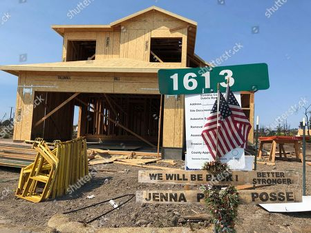 Signs and flags mark the partially rebuild home of Debbie and Rick Serdin in the Coffey Park neighborhood of Santa Rosa, Calif. The Trump administration's tariffs have raised the cost of imported lumber, drywall, nails and other key construction materials, squeezing homeowners who seek to rebuild quickly after losing their houses to natural disasters, such as the wildfires that destroyed Coffey Park