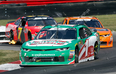 Elliott Sadler (1) leads Andy Lally (90) and Justin Allgaier (7) through a corner during the NASCAR Xfinity series auto race at Mid-Ohio Sports Car Course in Lexington, OH