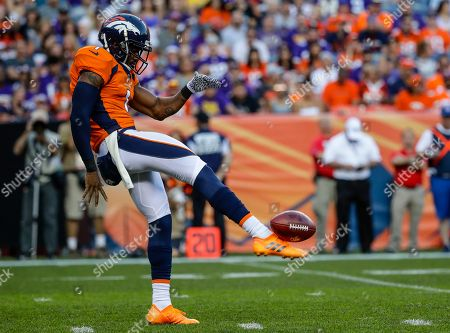 Denver Broncos punter Marquette King punts against the Minnesota Vikings during the first half in an NFL football game, in Denver