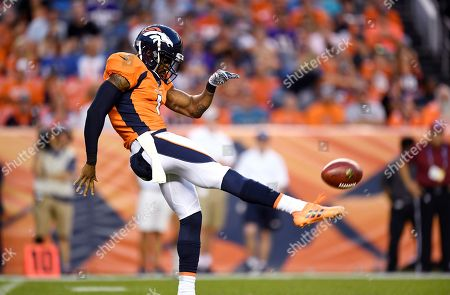 Denver Broncos punter Marquette King punts in the first half of an NFL football game against the Minnesota Vikings, in Denver