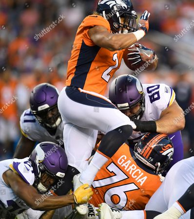 Phillip Lindsay, Mike Hughes. Denver Broncos running back Phillip Lindsay is stopped by Minnesota Vikings cornerback Mike Hughes in the first half of an NFL football game, in Denver