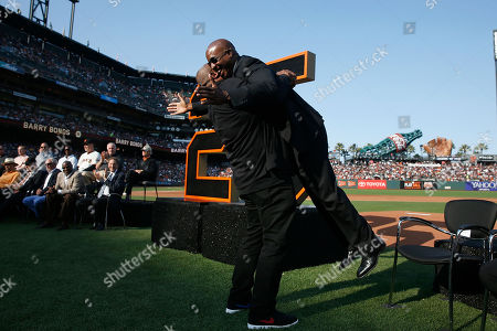 """Former San Francisco Giants player Barry Bonds (R) is lifted by former Pittsburgh Pirates teammate Bobby Bonilla (L) during a ceremony to retire his #25 jersey at AT&T Park in San Francisco, California, USA, 11 August 2018. Bond's late father, Bobby, who played for the Giants also wore jersey """"25"""".  Bond's holds the MLB record for most home run in a single season with 73 home runs, and for career home runs at 762."""