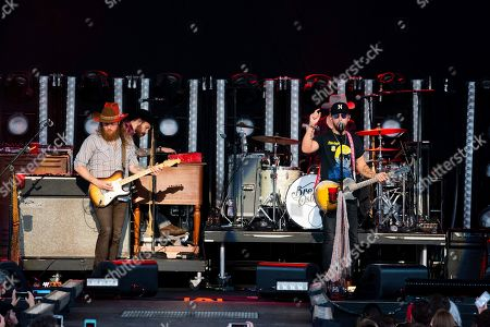 T. J. Osborne, John Osborne. Josh Osborne, left, and T. J. Osborne, of The Brothers Osborne perform on stage at Verizon Wireless Amphitheatre, in Alpharetta, Ga