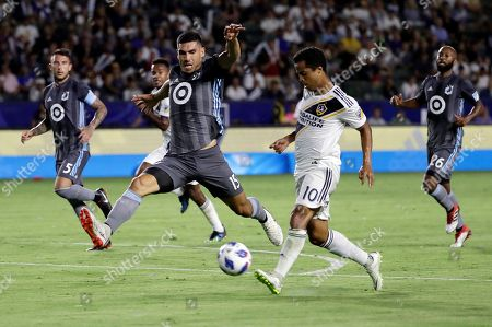 Giovani dos Santos, Michael Boxall. LA Galaxy Galaxy forward Giovani dos Santos, right, shoots next to Minnesota United defender Michael Boxall during the first half of an MLS soccer match, in Carson, Calif