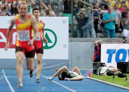 Germany's Lucas Jakubczyk, right, and Germany's Julian Reus, left, lie on the track after they collided during a men's 4 x 100 meter relay heat at the European Athletics Championships in Berlin, Germany