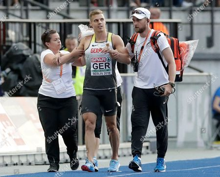Germany's Julian Reus, center is guided off the track after he collided with his teammate Lucas Jakubczyk, during a men's 4 x 100 meter relay heat at the European Athletics Championships in Berlin, Germany