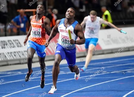 Britain's Harry Aikines-Aryeetey holds the baton after winning the gold medal in the men's 4x100-meter relay final at the European Athletics Championships in the Olympic stadium in Berlin, Germany