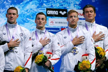 U.S. team members, from left to right, Ryan Murphy, Andrew Wilson, Caeleb Dressel, and Nathan Adrian, celebrate on the podium after winning the men's 4x100m medley relay final during the Pan Pacific swimming championships in Tokyo, Sunday, Aug.12, 2018