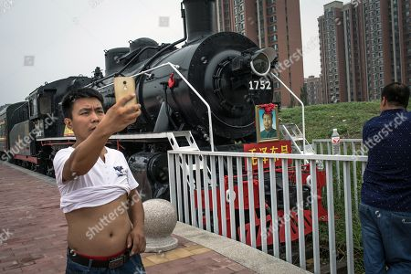 A Chinese man takes photos next to a steamtrain with a portrait of a former Chinese leader Mao Zedong on it, in Beijing, China, 12 August 2018.