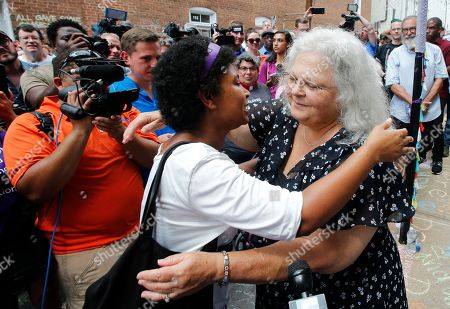 Susan Bro, right, mother of Heather Heyer who was killed during last year's Unite the Right rally, embraces a supporter after laying flowers at the spot her daughter was killed in Charlottesville, Va., . Last year, white supremacists and counterprotesters clashed in the city streets before a car driven into a crowd struck and killed Heyer