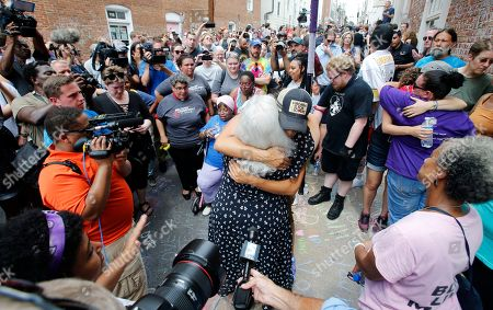 Susan Bro, center back to camera, mother of Heather Heyer who was killed during last year's Unite the Right rally, embraces a supporter after laying flowers at the spot her daughter was killed in Charlottesville, Va., . Last year, white supremacists and counterprotesters clashed in the city streets before a car driven into a crowd struck and killed Heyer