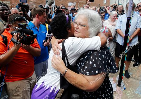 """Susan Bro, mother of Heather Heyer who was killed during last year's Unite the Right rally, embraces supporters after laying flowers at the spot her daughter was killed in Charlottesville, Va., . Bro said there's still """"so much healing to do."""" She said the city and the country have a """"huge racial problem"""" and that if it's not fixed, """"we'll be right back here in no time"""