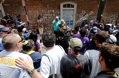 """Susan Bro, Kim Bro. Susan Bro, center right, mother of Heather Heyer who was killed during last year's Unite the Right rally, and her husband, Kim, center left, speak to supporters after laying flowers at the spot her daughter was killed in Charlottesville, Va., . Bro said there's still """"so much healing to do."""" She said the city and the country have a """"huge racial problem"""" and that if it's not fixed, """"we'll be right back here in no time"""