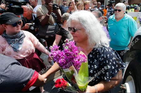 """Susan Bro, Kim Bro. Susan Bro, center, mother of Heather Heyer who was killed during last year's Unite the Right rally, and her husband, Kim, right, speak to supporters after laying flowers at the spot her daughter was killed in Charlottesville, Va., . Bro said there's still """"so much healing to do."""" She said the city and the country have a """"huge racial problem"""" and that if it's not fixed, """"we'll be right back here in no time"""