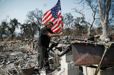 Freddie Cox plants a flag at the charred remnants of his godfather, Ed Bledsoe's home, in Redding, Calif. Bledsoe's wife, Melody, great-grandson James Roberts and great-granddaughter Emily Roberts were killed at the home in the Carr Fire